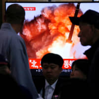 People watch a TV broadcast in Seoul on Oct. 31 showing file footage of a news report about North Korea firing two projectiles, possibly missiles, into the Sea of Japan. | REUTERS