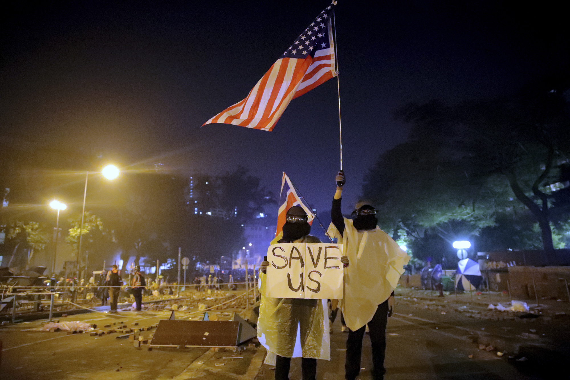 Protesters hold British and American flags and a sign reading 'Save Us' as they stand near Hong Kong Polytechnic University on Sunday. | AP