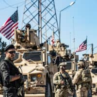 A member of the Kurdish People's Protection Units (left) stands guard as U.S. military armored vehicles and soldiers patrol near an oil well in Rumaylan (Rmeilan) in Syria's northeastern Hasakeh province on Wednesday. | AFP-JIJI