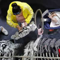 Woman shop at a fashion retailer during a sale at a shopping mall in Shenzhen, China, on Friday.   AP