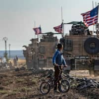 A Syrian boy on his bicycle looks at a convoy of U.S. armored vehicles patrolling fields near the northeastern Syria town of Qahtaniyah at the border with Turkey Thursday. U.S. forces accompanied by Kurdish fighters of the Syrian Democratic Forces (SDF) patrolled part of Syria's border with Turkey, in the first such move since Washington withdrew troops from the area earlier in October, an AFP correspondent reported. | AFP-JIJI
