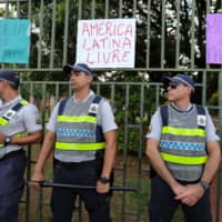 Members of the security forces stand guard outside the Venezuelan Embassy in Brasilia Wednesday. The placards read 'Latin America free,' 'Women against fascism' and 'Jail for the militiamen.' | REUTERS