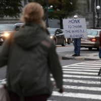 Julian, who only gave his first name in fear of his personal safety, stands on a corner with a sign supporting whistleblowers near the White House in Washington Wednesday. | REUTERS