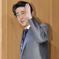 Prime Minister Shinzo Abe waves to reporters as he leaves the Prime Minister's Office on Monday. | KYODO