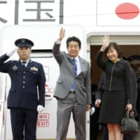 Prime Minister Shinzo Abe and his wife, Akie, wave Sunday at Haneda airport before departing for Bangkok to attend ASEAN-related meetings. At one, he will discuss the Regional Comprehensive Economic Partnership trade agreement. | KYODO