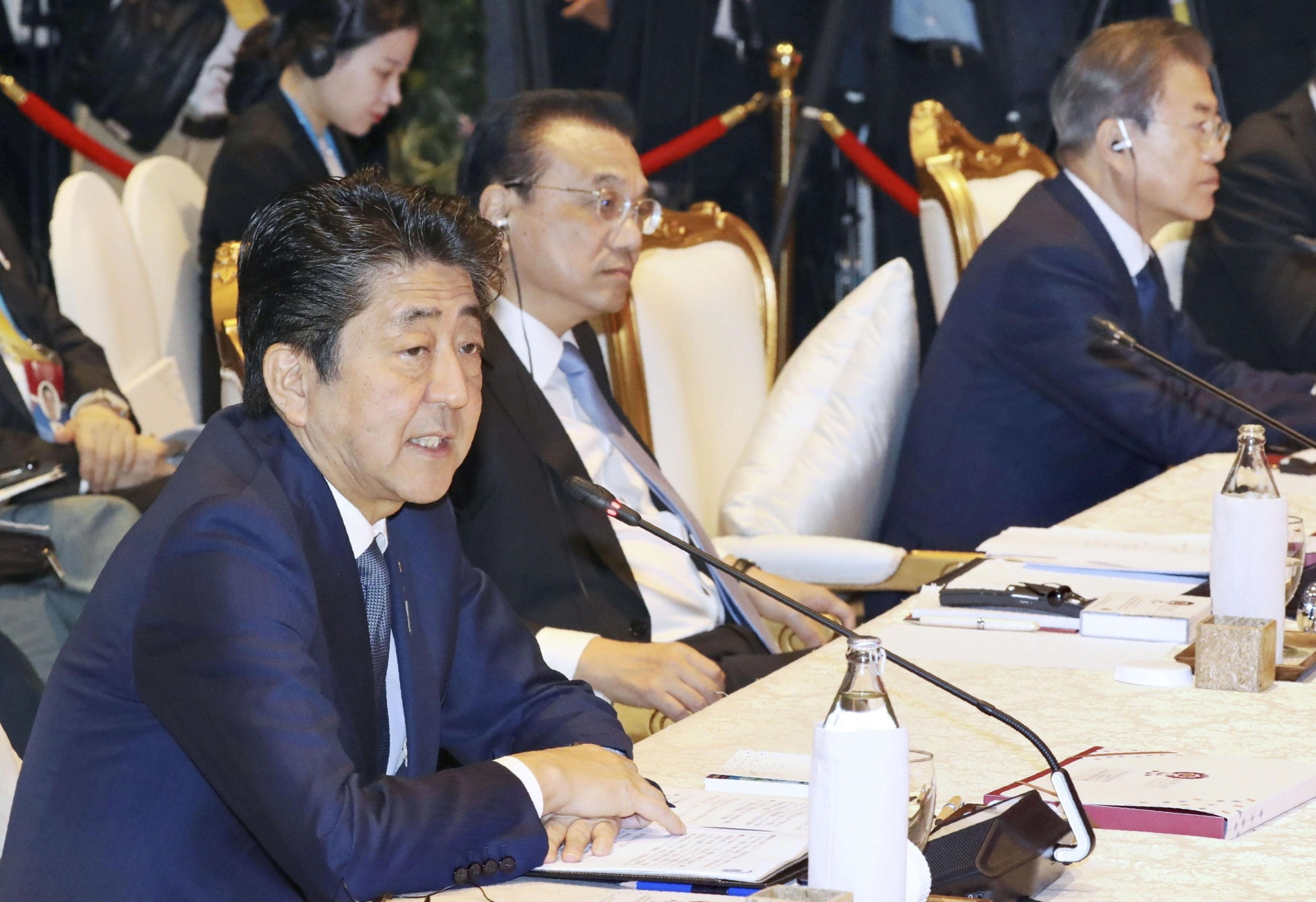 Prime Minister Shinzo Abe (left) attends a meeting of the Association of Southeast Asian Nations leaders plus Japan, China and South Korea in Bangkok on Monday along with Chinese Premier Li Keqiang (center) and South Korean President Moon Jae-in (right). | POOL / VIA KYODO