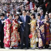 Prime Minister Shinzo Abe smiles with kimomo-clad attendees at a cherry blossom-viewing event on April 13 at Shinjuku Gyoen National Garden in Tokyo. | KYODO