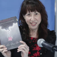 Kathleen Burkinshaw, author of 'The Last Cherry Blossom,' holds up a copy of her book at the U.N. on Nov. 5. | GETTY IMAGES