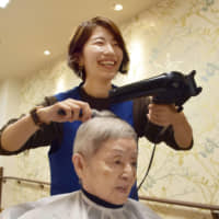 Masueko Imai, 86, a resident of a nursing home in Setagaya Ward, Tokyo, gets a haircut and set from a beautician visiting the facility. | KYODO
