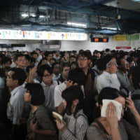 Commuters wait for platforms to open at Shinjuku Station on Sept. 9. Typhoon Faxai's assault on the Kanto region earlier in the day left train services suspended.  | AP