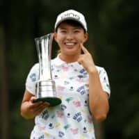 Hinako Shibuno holds the trophy as she poses for photos following her victory at the Women's British Open in August in Milton Keynes, England. |  ACTION IMAGES VIA REUTERS