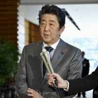 Prime Minister Shinzo Abe speaks to reporters Monday at his office in Tokyo. | KYODO