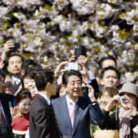 Prime Minister Shinzo Abe is surrounded by guests during a cherry blossom-viewing event in April in Tokyo.   KYODO