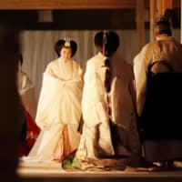 Empress Masako heads to the Choden, part of the gigantic Daijokyu Halls, for the 'Daijokyu no gi' main rite of the Daijosai great thanksgiving ceremony on the Imperial Palace grounds in Tokyo on Thursday evening. | KYODO