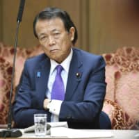 Deputy Prime Minister Taro Aso attends a Diet session Thursday in Tokyo. | KYODO