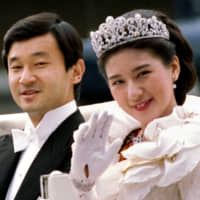 Then-Crown Princess Masako waves to Imperial Household staffers alongside then-Crown Prince Naruhito as they depart for their wedding parade in Tokyo on June 9, 1993.   REUTERS