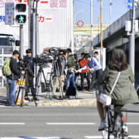 Reporters gather Saturday near the site where Ryotaro Oue, who has been indicted for using illegal stimulants and possessing marijuana, escaped in Higashiosaka, Osaka Prefecture. He was re-apprehended on Monday. | KYODO