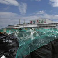 Bags of radioactive waste are seen outside an incineration facility in Tomioka, Fukushima Prefecture, in 2016. Dozens of bags containing radioactive waste are still missing in the prefecture three weeks after they were swept away from storage areas in floods triggered by Typhoon Hagibis. | AP