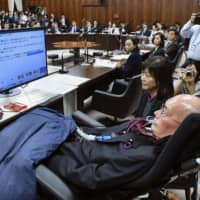 Yasuhiko Funago, a lawmaker with ALS, asks a question during a House of Councilors committee session in Tokyo on Thursday using a computerized speech synthesizer. | KYODO