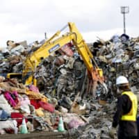 Disaster waste from Typhoon Hagibis is piled up in Marumori, Miyagi Prefecture, on Tuesday, a month after the powerful storm hit wide areas of the country. | KYODO