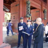 Tokyo Fire Department officials offer fire prevention guidance to a monk at Zojoji temple in Tokyo's Minato Ward in April following a fire that badly damaged part of the roof of  Notre Dame Cathedral in Paris the same month. | KYODO