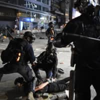 Police officers pin down a protester near Hong Kong Polytechnic University on Monday evening. | KYODO