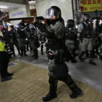 A police officer points his shotgun at protesters during a clash in Hong Kong early Saturday. | AP