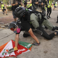 A police officer pins down a student during a clash with protesters and police at the Chinese University in Hong Kong on Tuesday. Foreign Minister Toshimitsu Motegi told reporters in Tokyo a Japanese man was injured amid the escalating protest and received treatment at a hospital. | AP