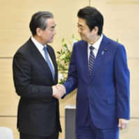 Visiting Chinese foreign minister Wang Yi shakes hands with Prime Minister Shinzo Abe during their meeting at the Prime Minister's Office on Monday.   KYODO