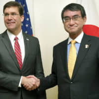 U.S. Defense Secretary Mark Esper and Defense Minister Taro Kono shake hands after meeting Monday in Bangkok on the sidelines of an expanded defense meeting of the Association of Southeast Asian Nations. | KYODO
