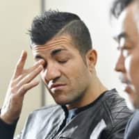 A Kurdish man, who has sued Japan's government for leaving him untreated for cancer during his detention in Ibaraki Prefecture, wipes his eye during a news conference in Tokyo on Tuesday. | KYODO