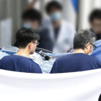 Shinji Aoba, the suspect in a deadly arson attack on a Kyoto Animation Co. studio in July, is carried on a stretcher to a Kyoto hospital Thursday from one in Osaka Prefecture after undergoing multiple skin grafts. | KYODO