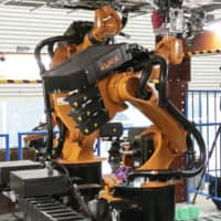 Shimizu Corp.'s Robo-Buddy carries out the final stage of finishing ceilings. | KYODO