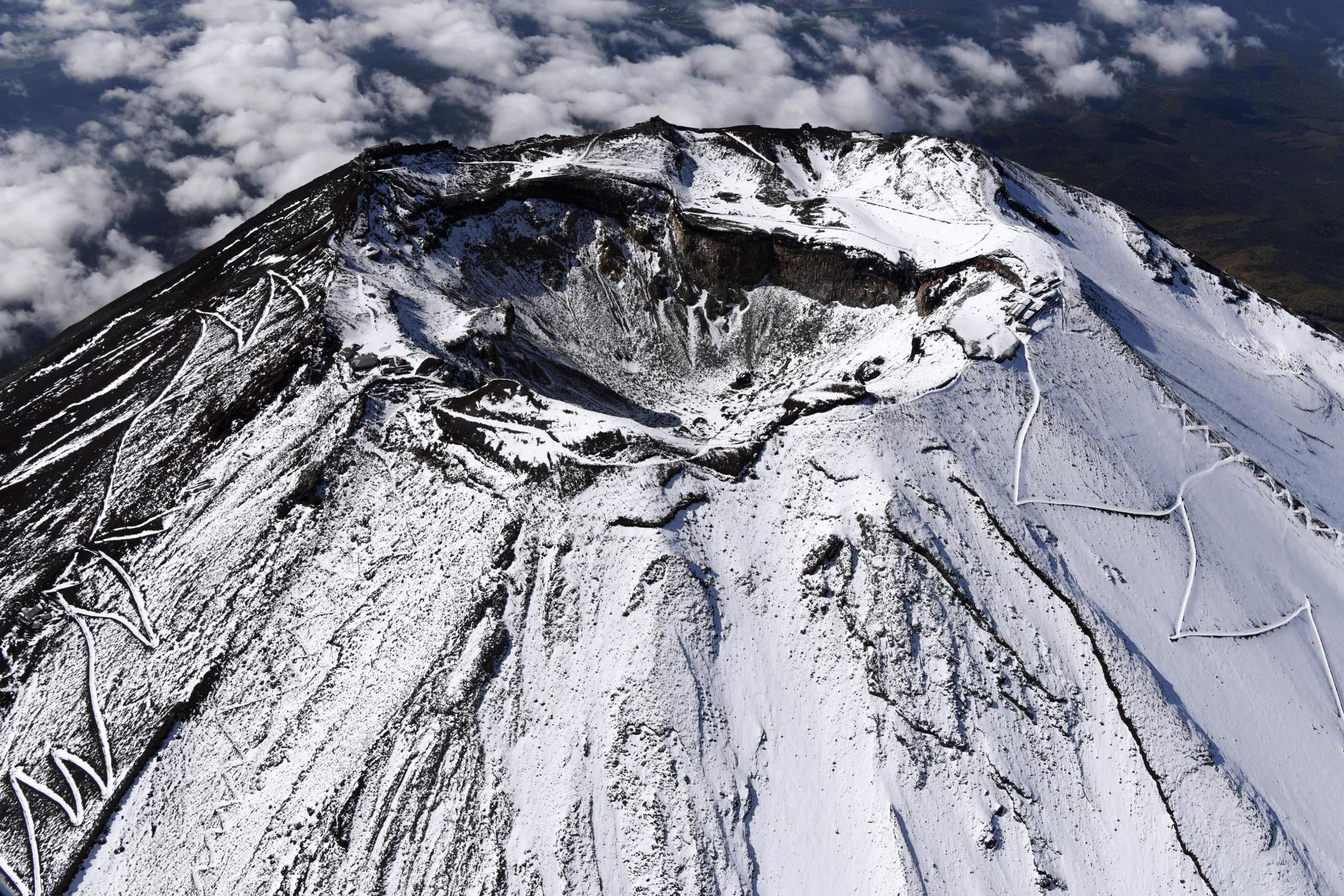 Mount Fuji's first snowcap of the season is seen on Oct. 23, a week before a 47-year-old man from Tokyo livestreamed his fatal fall from the summit. | KYODO