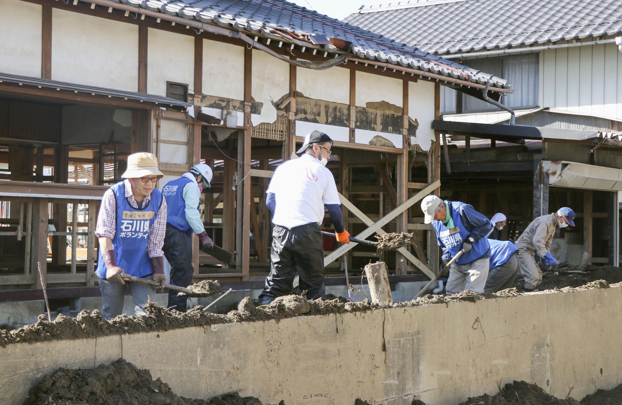 Volunteers on Nov. 2 help clean up mud at a house in the city of Nagano that was flooded after Typhoon Hagibis. | KYODO