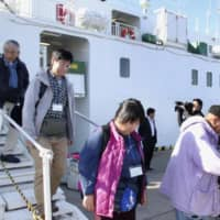 Japanese tourists who went to the Northern Territories disembark at Nemuro port in east Hokkaido on Saturday.   KYODO