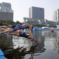 Triathletes dive into the water at a world triathlon mixed relay event at Odaiba Marine Park in Tokyo in August. | KYODO