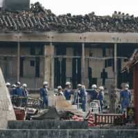Firefighters inspect Shuri Castle in Naha, Okinawa Prefecture, on Nov. 2 after a fire engulfed it two days earlier. | KYODO