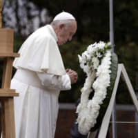 Pope Francis offers a prayer after laying a wreath at Nagasaki Peace Park on Sunday. | AP