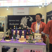 Akinori Oishi (right), general manager of Ikekame Shuzo Co., promotes sake at the second annual China International Import Expo on Nov. 6 in Shanghai. | KYODO
