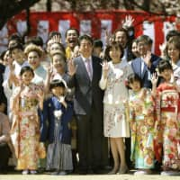 Prime Minister Shinzo Abe (center) and his wife, Akie, pose for a photo with attendees at a cherry blossom-viewing event held April 13 at Shinjuku Gyoen National Garden in Tokyo. | KYODO