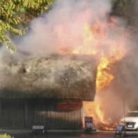 A photo provided by a local shop shows a hut engulfed in flames in a parking lot near the historic Shirakawa-go village in Gifu Prefecture on Monday. | KYODO