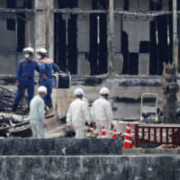 Firefighters conduct an investigation in the remains of Shuri Castle's Seiden main hall in Naha, Okinawa Prefecture, on Tuesday. Buildings located together with the UNESCO World Heritage site were destroyed by a major fire last week. | KYODO