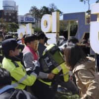 Protesters attempting to put up an anti-Japan signboard at a park near the Consulate General of Japan in Busan, South Korea, jostle with police officers on Oct. 30.   KYODO