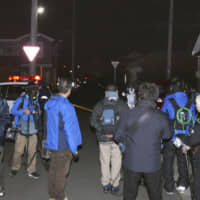 Reporters stand on a road in Hachinohe, Aomori Prefecture, where a girl was assaulted by an attacker with a knife on Tuesday evening.
