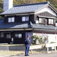 A police officer stands near a house in the city of Tsuruga, Fukui Prefecture, on Sunday where the bodies of three people were found. | KYODO