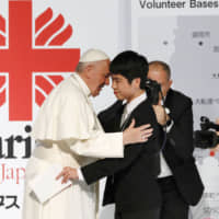 Pope Francis hugs high school student Matsuki Kamoshita in Tokyo on Monday during a meeting with victims of the March 2011 earthquake and tsunami that devastated northeastern Japan.   KYODO