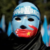 Speaking out: An ethnic Uighur demonstrator wears a mask as she attends a protest against China in front of the Chinese Consulate in Istanbul. | REUTERS