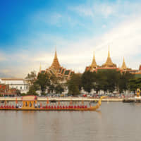 What fun: A barge passes in front of Wat Pho, which sits on the banks of Bangkok's Chao Phraya River.   GETTY IMAGES