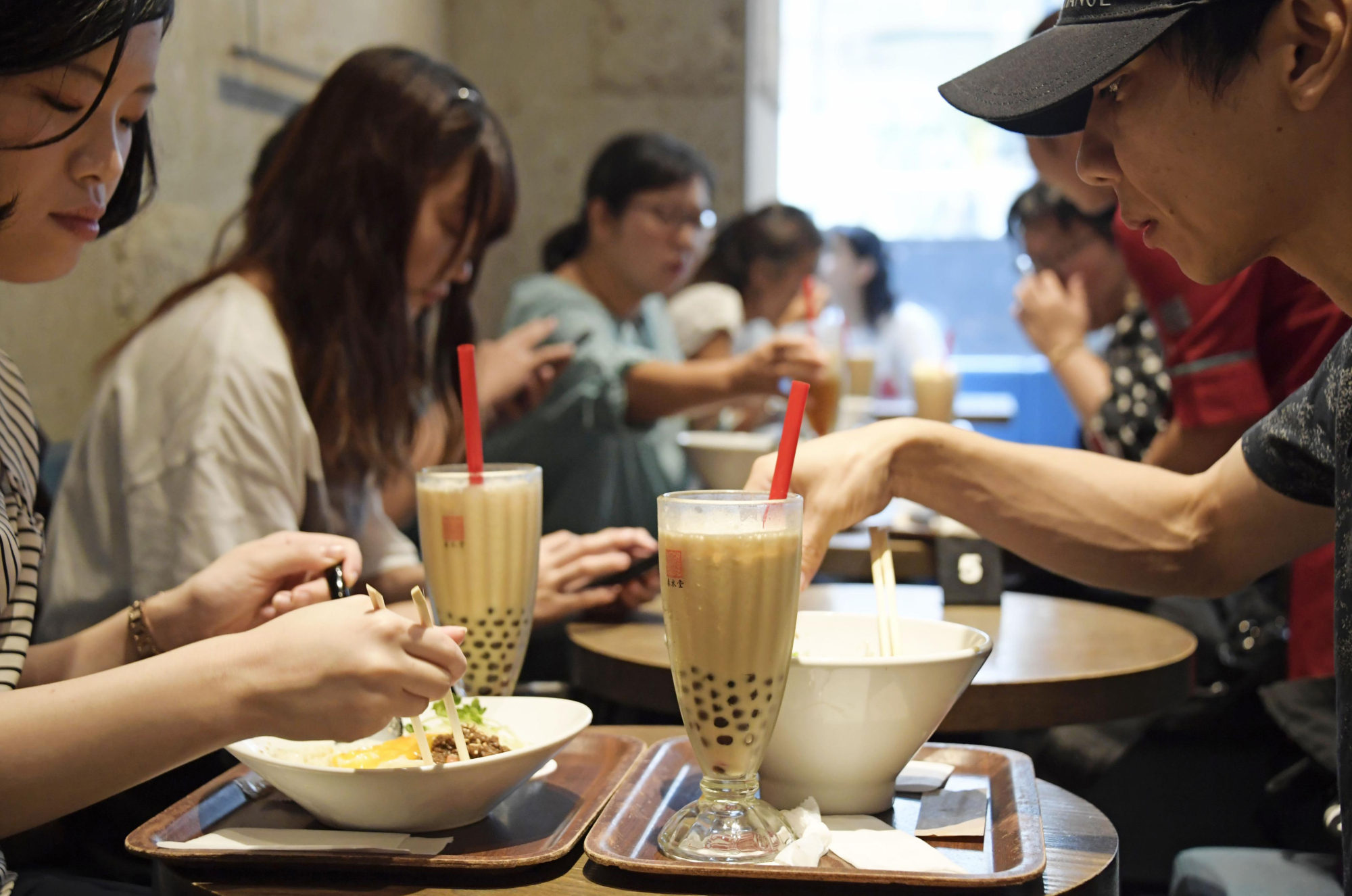 Squishy, chewy and filling: Customers enjoy bubble tea at one of Chun Shui Tang's Japan outlets. The Taiwanese tea shop claims to have invented bubble milk tea.   KYODO
